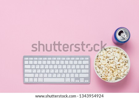 Keyboard, can with a drink and a bowl of popcorn on a pink background. The concept of watching movies, TV shows and shows online. Flat lay, top view. #1343954924
