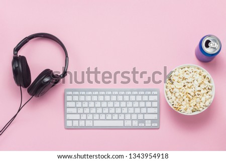 Keyboard, can with a drink, headphones and a bowl of popcorn on a pink background. The concept of watching movies, TV shows and shows online, format PPV. Flat lay, top view. #1343954918