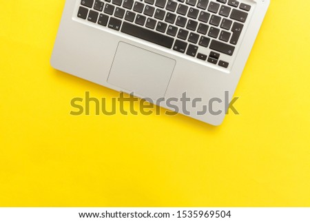 Keyboard laptop computer isolated on yellow desk background. Modern Information technology and sofware advances. Freelance home office programmer or designer workspace concept #1535969504
