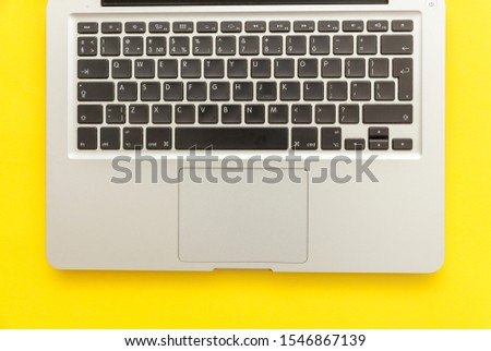 Keyboard laptop computer isolated on yellow desk background. Modern Information technology and sofware advances. Freelance home office programmer or designer workspace concept #1546867139
