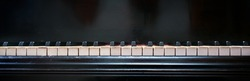 Keyboard of an old grand piano with white and black keys from ivory and ebony, panoramic format with copy space, selected focus