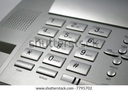 Keyboard of grey telephone by a large plan