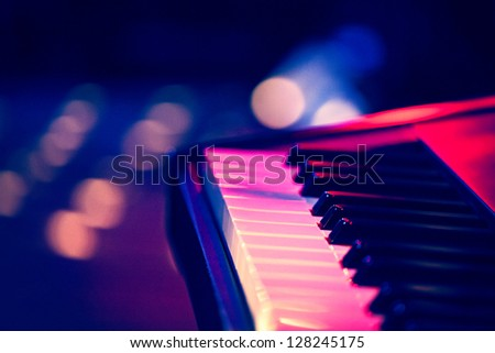 Keyboard on stage under multicolored lights with grain added