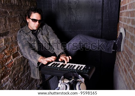 Keyboard player grooving on synthesizer in basement