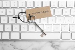 Keyboard, vintage key and tag with word KEYWORDS on white marble table, top view