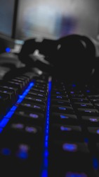 Keyboard with back lit keys close up with computer screen and headphones in background
