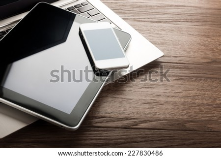 keyboard with  phone and tablet pc on wooden desk - Shutterstock ID 227830486