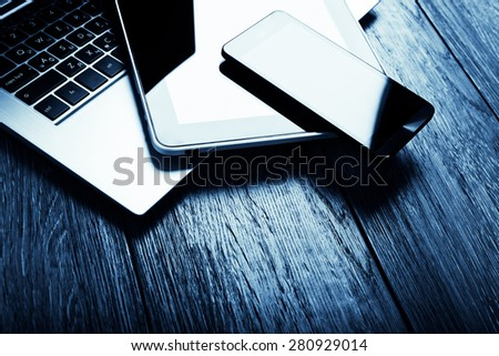 keyboard with phone and tablet pc on wooden desk.  Blue toned - Shutterstock ID 280929014