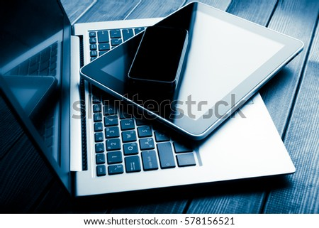 keyboard with phone and tablet pc on wooden desk. Blue toned