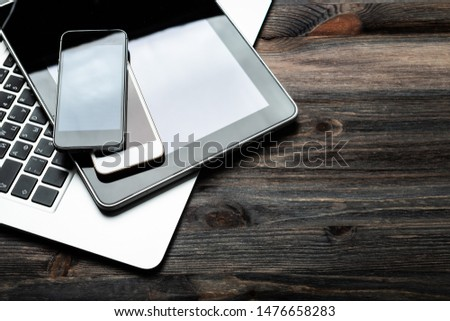 keyboard with two phones and tablet pc on wooden desk