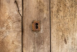 Keyhole and old metal escutcheon on a distressed grungy wooden door, close up texture view