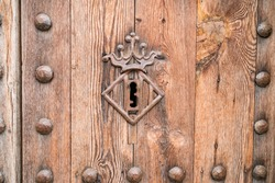Keyhole decorated with heraldic crown symbol on the wooden door of the Torres de Quart. Torres de Quart - the western city gate of Valencia old town.