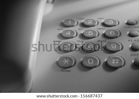 Keypad with numbers for dialling and function buttons on a landline telephone instrument in blue light