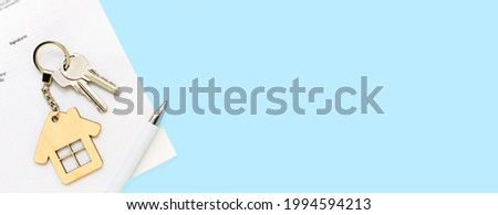 Keys and house keychain on real estate mortgage loan document, contract agreement to buy or construction new home, insurance, registration of lease, rent apartments. Blue banner background, copyspace.