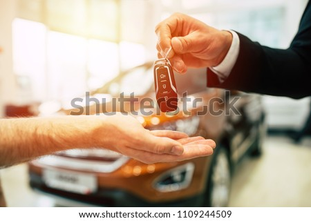 Keys from new car, young salesman transfer the car key in hand of customer in casual wear on dealership background Foto stock ©
