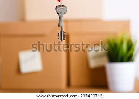 Keys over pile of brown cardboard boxes with house or office goods background. Moving to new place of living concept.