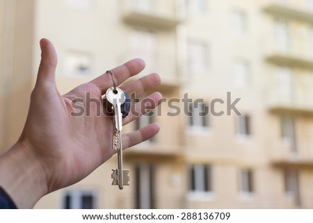 keys to the apartment in his left hand against the background of high-rise buildings