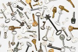 Keys to the locks. Many different keys to the locks lie on a white surface