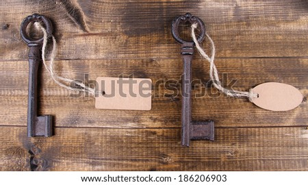 Keys with empty tag, on color wooden background