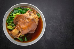 Kha Moo Pa Lo, Thai food, brown Chinese stewed pork leg in sweet brown sauce on dark tone texture background with copy space for text, top view shot