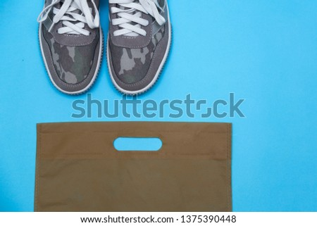 Khaki color sneakers. Gray sneakers on a blue background. Sneakers and packaging