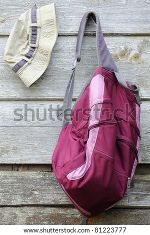 Khaki hat and purple backpack on the shabby wooden wall