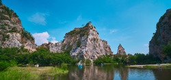 Khao Ngu Stone Park in Ratchaburi, Thailand also call Snake Mountain. A stone mountain with peak in middle with blue sky and lake in front.