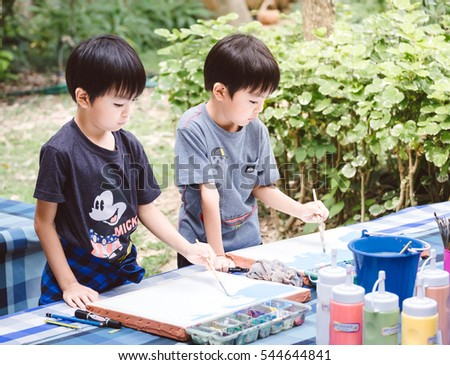 Khao Yai, Thailand - December 3, 2016 : two boys draw and paint picture in the park