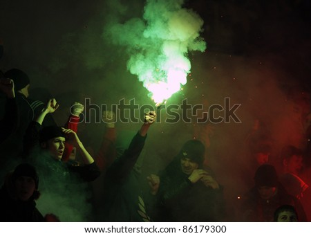 KHARKIV, UA - MARCH 13: FC Metalist Kharkiv fans burn flares during soccer match vs. FC Dnipro Dnipropetrovsk, March 13, 2011 in Kharkov, Ukraine