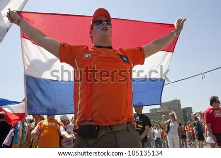 KHARKIV, UKRAINE  JUNE 13: Dutch fan holding a national flag before a UEFA Euro 2012 football match between Germany and Netherlands on June 13, 2012 in Kharkiv, Ukraine