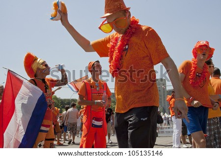 KHARKIV, UKRAINE  JUNE 13: Dutch fans wearing clothes with national team colors before a UEFA Euro 2012 football match between Germany and Netherlands on June 13, 2012 in Kharkiv, Ukraine - stock photo