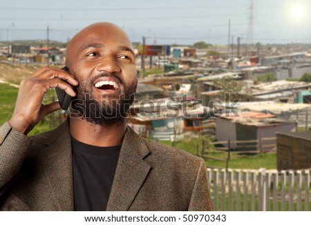 Khayalitsha Township in background with successful businessman talking on cellphone in foreground.
