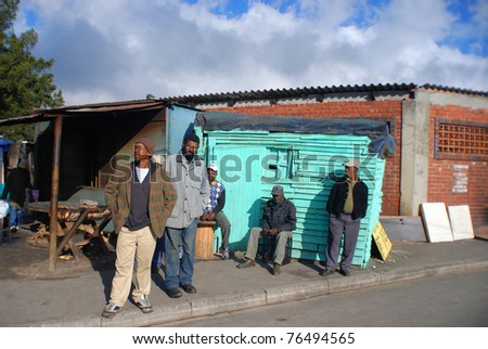 KHAYELITSHA, CAPE TOWN - MAY 22 : A unidentified group of man wait on the side of a street in Khayelitsha township, on May 22, 2007, Cape Town, South Africa