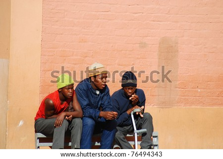 KHAYELITSHA, CAPE TOWN - MAY 22 : A unidentified group of young teenagers sit on the side of a street in Khayelitsha township, on May 22, 2007, Cape Town, South Africa