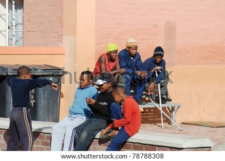 KHAYELITSHA, CAPE TOWN - MAY 22 : A unidentified group of young teenagers sit on the side of a street in Khayelitsha township, the name is Xhosa for New Home, on May 22, 2007, Cape Town, South Africa