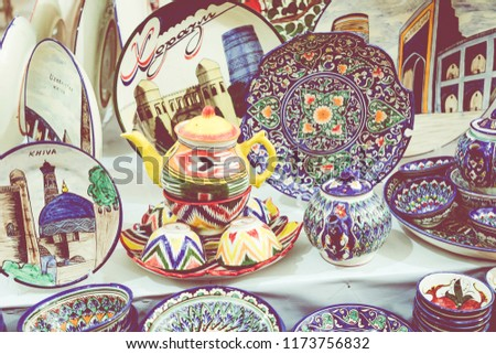 KHIVA, UZBEKISTAN - AUGUST 26, 2018: Plates and pots on a street market in the city of Khiva Uzbekistan. #1173756832
