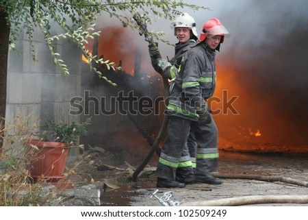 KHMELNITSKY, UKRAINE - OCTOBER 11: fire department in action during burning warehouses with plastic products, October 11, 2011 in Khmelnitsky, Ukraine