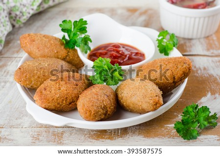 Kibbeh - traditional Arabian meatballs, minsed meat and bulgur or rice wheat fried snack with parsley, ketchup in white plate on wooden background. Eastern cuisine. Selective focus
