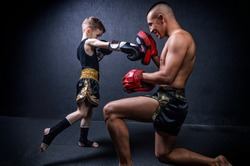 Kickboxing coach is training the boy. The concept of family, sports, mma, muay thai. Mixed media