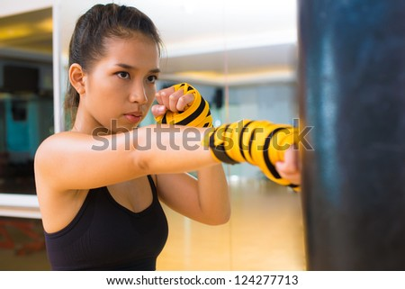 Kickboxing girl practicing with a punching bag