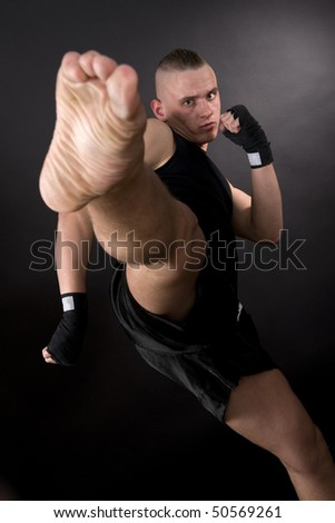 Kicking man with scar face in motion on dark background. Focus on face