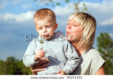 Kid and mother blowing dandelion. Spring time