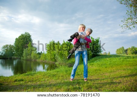 Kid and mother having fun outdoors. Happy spring time - stock photo