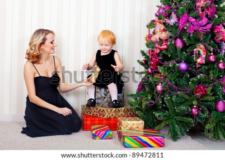 Kid and mother near new-year tree