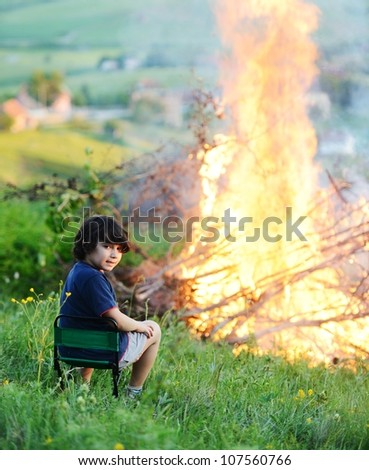 Kid beside the big fire
