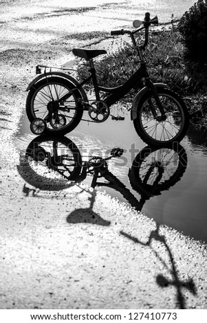 Kid bicycle in a puddle; after rain