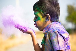 Kid blowing holi colour powder from hand during Holi festival celebration - Concept of young kids having fun by playing holi during festive