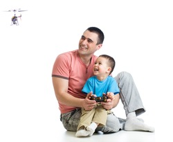 Kid boy and dad playing with RC helicopter toy