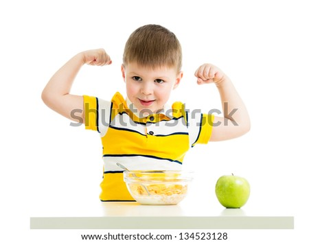 kid boy eating healthy food and showing his strength