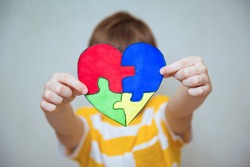 Kid boy hands holding drawing of a heart, child mental health concept, world autism awareness day, teen autism spectrum disorder awareness concept
